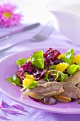 Duck breast with salad leaves, orange segments and grapes