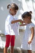 Two little girls drinking juice