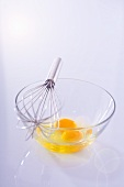 Egg yolks in glass bowl with whisk
