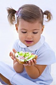 Little girl holding slice of bread with quark, cucumber and radishes
