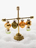 Christmas tree ornaments hanging on stand in snow