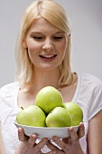 Blond woman holding dish of green apples