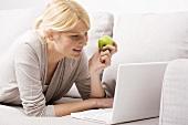 Blond woman eating apple
