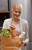 Blond woman with bag of shopping in kitchen