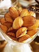 Freshly baked madeleines in glass dish