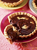Small chocolate tart with gold leaf on gold-rimmed saucer