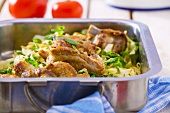 Roasted pork ribs with cabbage in roasting tin