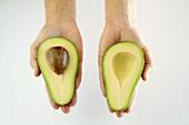 Hände halten zwei Avocadohälften