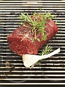 Beef fillet with herbs and garlic on barbecue rack
