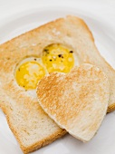Fried eggs in slice of toast and toast heart