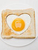 Heart-shaped fried egg in slice of toast