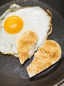 Fried egg and broken toast heart in frying pan