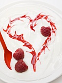 Yoghurt with raspberries and heart drawn in raspberry sauce