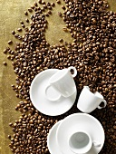 White espresso cups and saucers on coffee beans