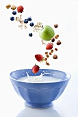Cereal, fruit and nuts falling into cereal bowl