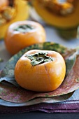 Persimmons on leaves, pumpkins in background