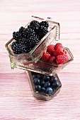 Blackberries, raspberries and blueberries in glass receptacles