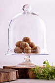 Eggs boiled in tea on cake stand with glass dome