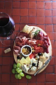 Antipasti platter with sausage and cheese, glass of red wine