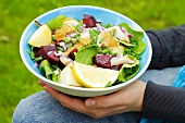 Person holding bowl of salad (beetroot, herring, potatoes)