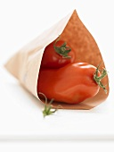 Two plum tomatoes in paper bag
