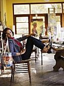Frau sitzt auf einem Stuhl, mit den Füssen am Tisch