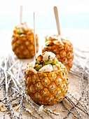 Papaya, lychee & melon salad with coconut flakes in hollowed-out coconuts