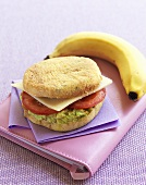English muffin filled with avocado salad & banana on appointment diary