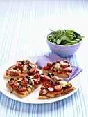 Slices of pizza topped with tomatoes and olives
