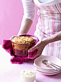 A woman serving a plum and almond bake