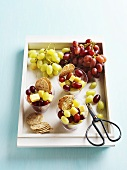 A tray of snacks - grapes, cheese cubes and crackers