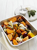 Root vegetables, onions and thyme in roasting dish