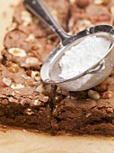 Nut brownies and sieve with icing sugar