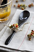 A wooden spoon decorated with berries on a linen cloth