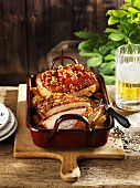 Roast pork with crackling in roasting dish, beer