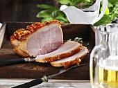 Roast cured pork with crackling, partly carved