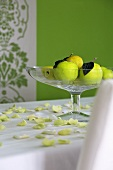 Green apples in glass fruit bowl on white table cloth scattered with yellowy-green petals