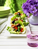 Vegetable salad with pancetta on lettuce leaves