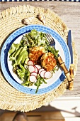 Salmon cakes with radishes, avocado and green salad