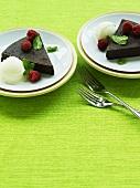 Slices of chocolate tart with vanilla ice cream and raspberries