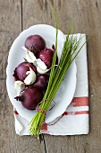 Red onions, garlic and chives on a plate