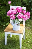 Peonies in enamel pot on garden chair
