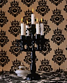 A black candle holder against black and white wallpaper