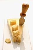 Ein Stück Parmesan mit Käsemesser