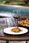 Paella und Rotweinglas auf Tisch am Swimmingpool