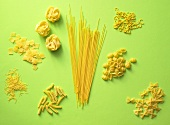 Various types of pasta on a green surface