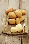 New potatoes, some peeled, on a hessian sack