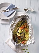 Trout with vegetables and gooseberries baked in aluminium foil