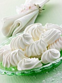 Meringues on a green plate with a napkin in the background