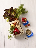 Fresh vegetables in a wooden basket, strawberries and seeds